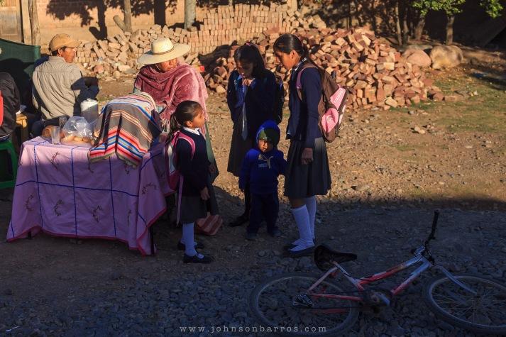 Crianças tomam café na rua antes de ir para o colégio